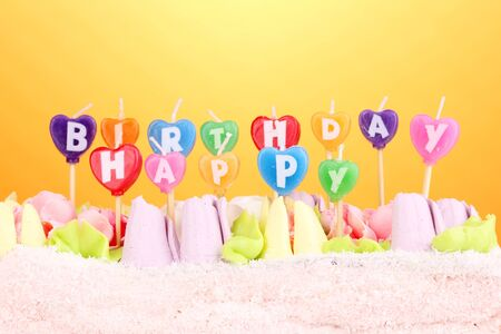 Birthday cake with candles on yellow background photo