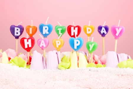 Birthday cake with candles on pink background photo