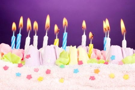 Birthday cake with candles on violet background photo