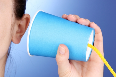 Human ear and paper cup near it close-up on blue background Stock Photo - 13796842