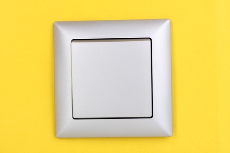 Modern light switch on yellow background photo