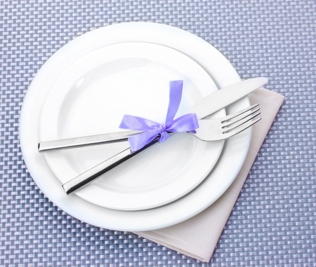White empty plates with fork and knife tied with a ribbon on a grey tablecloth photo