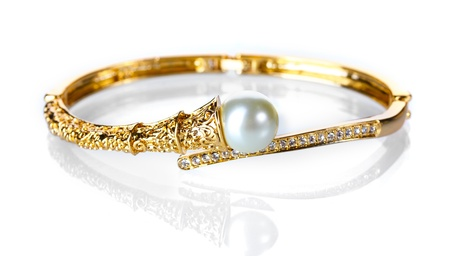 Beautiful golden bracelet with pearl on isolated on white photo