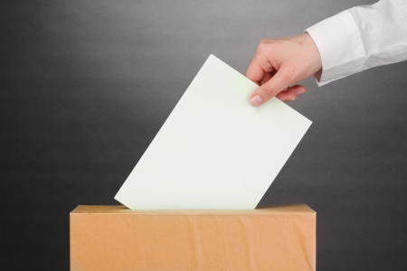 Hand with voting ballot and box on grey background Stock Photo - 13794506