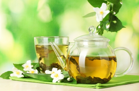 tea garden: green tea with jasmine in cup and teapot on wooden table on green background Stock Photo