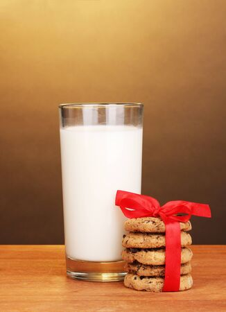 Glass of milk and cookies on wooden table on brown background photo