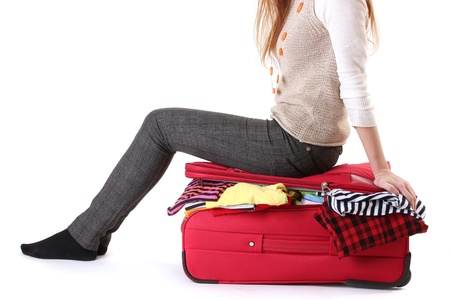 packing suitcase: Girl sitting on a suitcase and tries close it isolated on a white Stock Photo