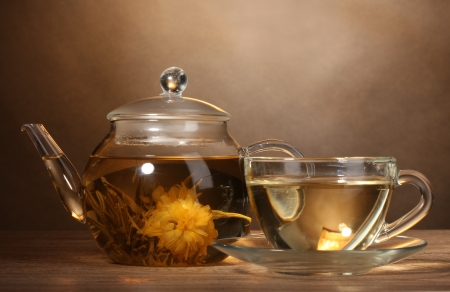 glass teapot and cup with exotic green tea on wooden table on brown background photo