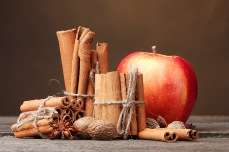 apple christmas: Cinnamon sticks,red apple, nutmeg,and anise on wooden table on brown background