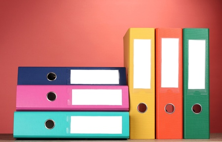 bright office folders on wooden table on red background photo
