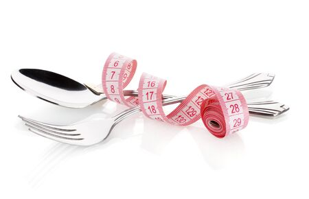 Fork, spoon and measuring tape isolated on white photo