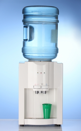 Electric water cooler on blue background photo