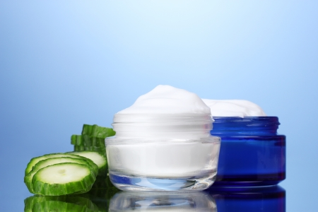 health care protection: cream and fresh sliced cucumber on blue background