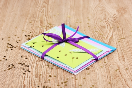 Bunch of color envelopes with ribbon and confetti on wooden background Stock Photo - 13822211