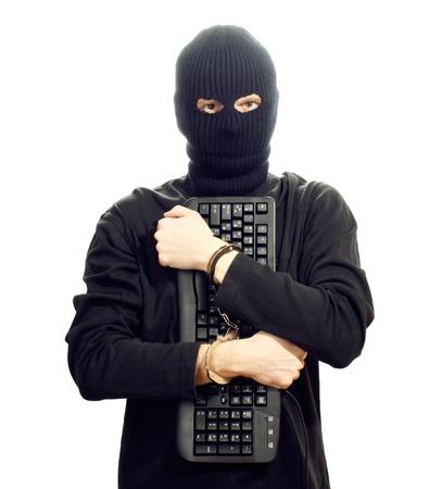 hijacker: Hacker en el antifaz negro con las manos esposadas con teclado aislado en blanco