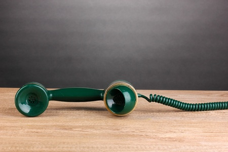 Handset of retro phone on wooden table on grey background photo