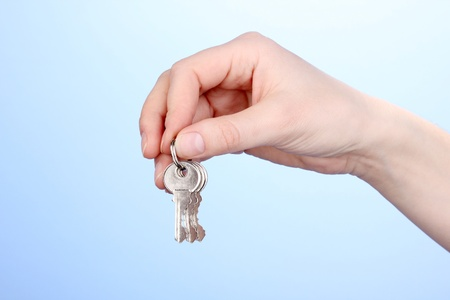 Key in hand on blue background Stock Photo - 13820003