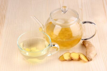 Healthy ginger tea in kettle and cup on wooden background photo