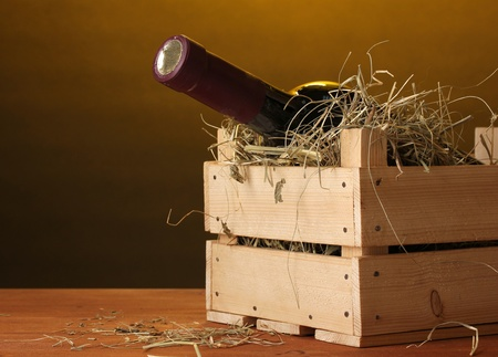 Bottle of great wine in crate on wooden table on brown background photo