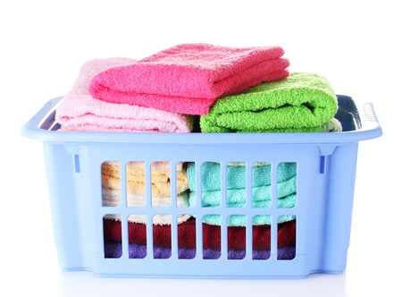 neatly stacked: Plastic basket with bright towels isolated on white