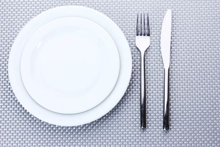 White empty plates with fork and knife on a grey tablecloth Stock Photo - 13821954