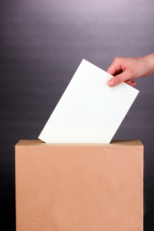 political system: Hand with voting ballot and box on grey background