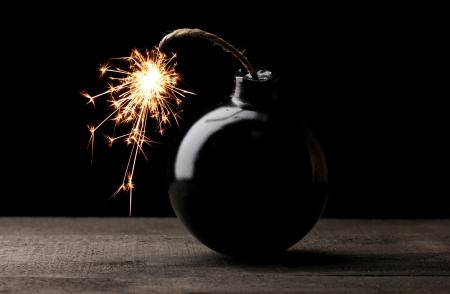 Cartoon style bomb on wooden table on black background Stock Photo