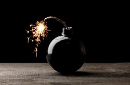 Cartoon style bomb on wooden table on black background Stock Photo - 13818927