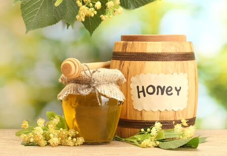 jar and barrel with linden honey and flowers on wooden table on green background Stock Photo - 13866051