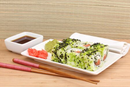 Tasty rolls served on white plate with chopsticks on wooden table on light background Stock Photo - 13866024