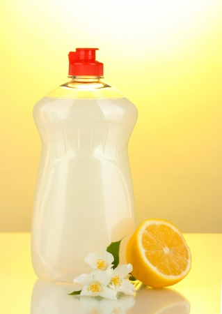 Dishwashing liquid, lemon and flowers on yellow background photo