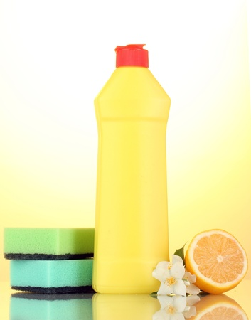 Dishwashing liquid with sponges and lemon with flowers on yellow background photo