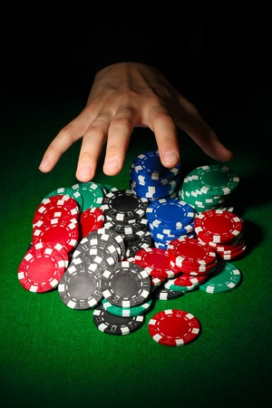 Poker chips and hand above it on green table photo