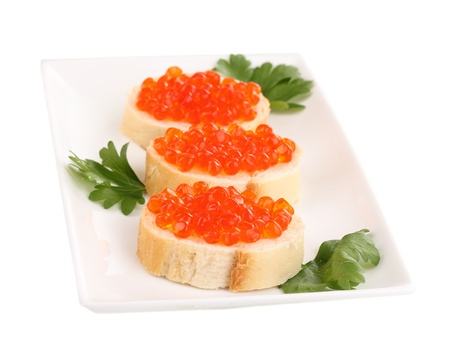 Red caviar on bread on white plate isolated on white photo