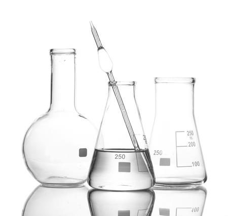 Un recipiente con agua y dos frascos vacíos con la reflexión aislada en blanco Foto de archivo