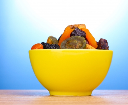 Dried fruits in bright bowl on wooden table on blue background photo