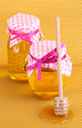 Jars of honey and wooden drizzler on yellow honeycomb background  photo