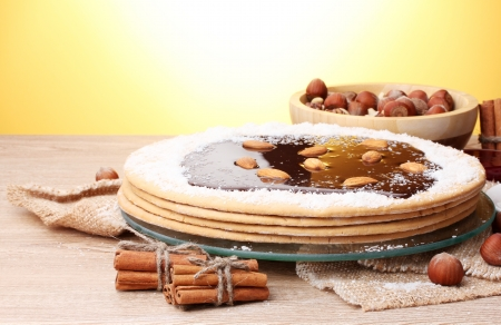 cake on glass stand and nuts on wooden  table on yellow background Stock Photo - 13866041