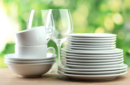 Clean dishes on wooden table on green background photo