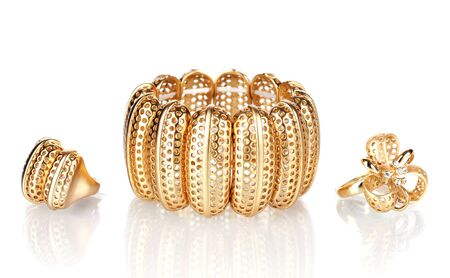 Beautiful golden bracelet and rings isolated on white Stock Photo - 13864454