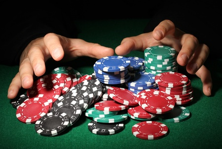 taking risks: Poker chips and hands above it on green table