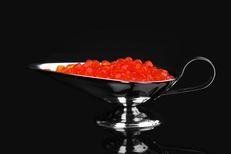 Red caviar in silver bowl isolated on black Stock Photo - 13878206