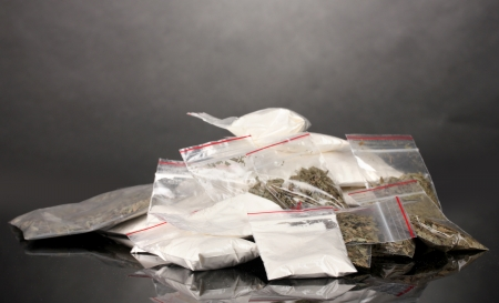 illegal drugs: Cocaine and marihuana in packages on grey background Stock Photo