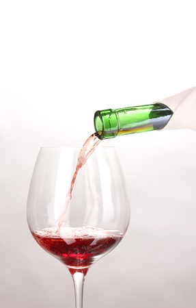 claret: Pouring wine into wineglass isolated on white