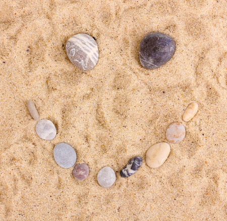 Smile-stones on sand photo