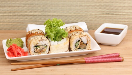 Tasty rolls served on white plate with chopsticks on wooden table on light background Stock Photo - 13922479