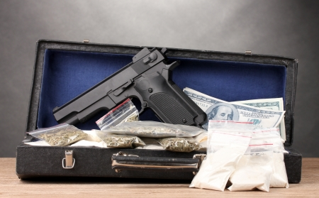 Cocaine, marijuana dollars and handgun in case on wooden table on grey background photo