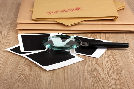 Envelopes with top secret stamp with photo papers and magnifying glass on wooden background photo