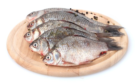 Fresh fishes with spice on wooden cutting board isolated on white photo