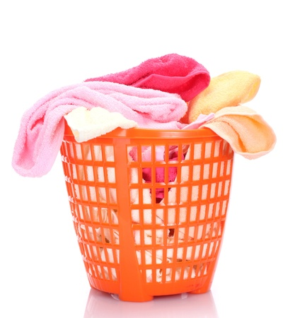 Plastic basket with bright towels isolated on white photo